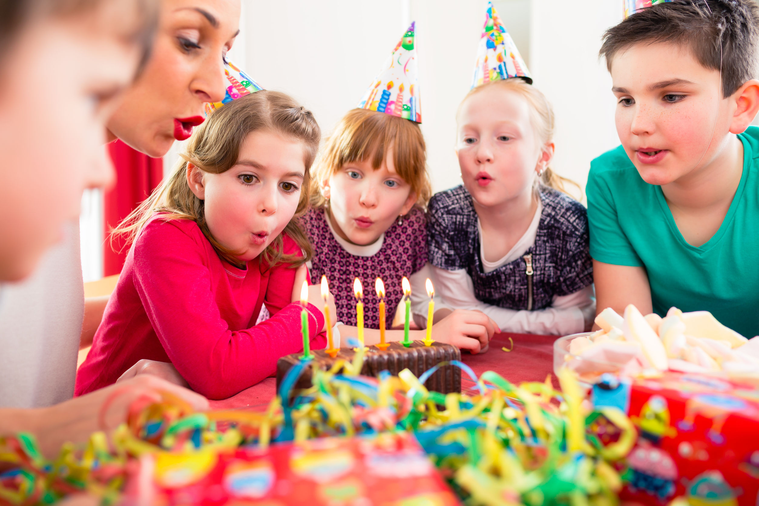 51585948 - child on birthday party blowing candles on cake being helped by friends and the mother